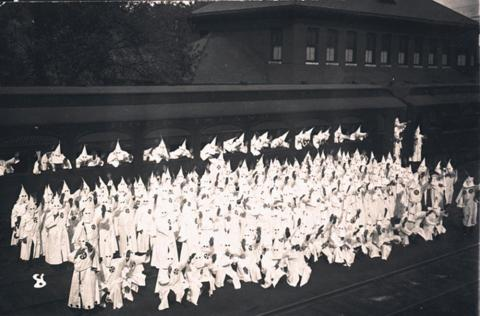 Klan members posed by train car